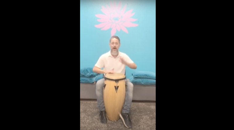 Mr. Pablo plays a bongo drum in a room with blue walls and a stencil of a lavender lotus.