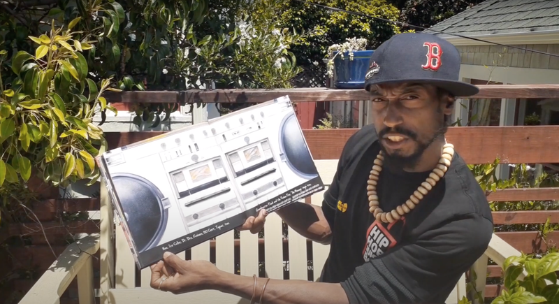 "Mr. Rha opens ""The Roots of Rap"" to a page with an illustration of a boombox."