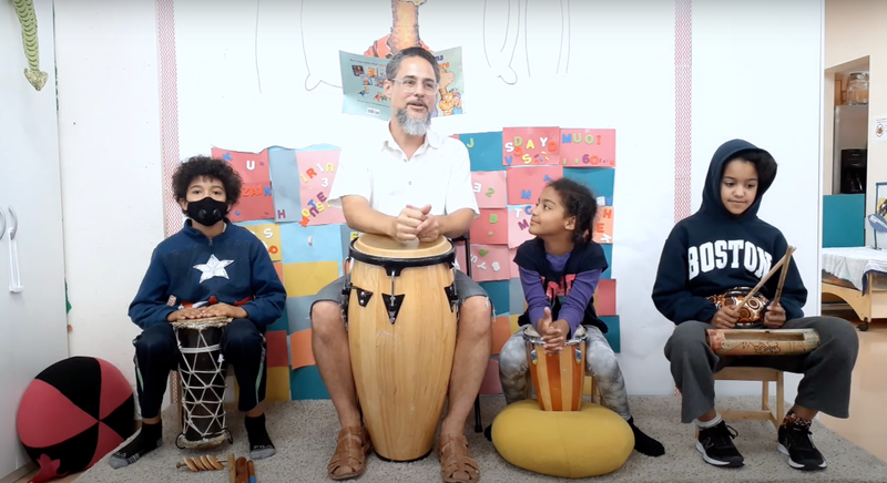Mr. Pablo and friends sit together with drums and instruments.