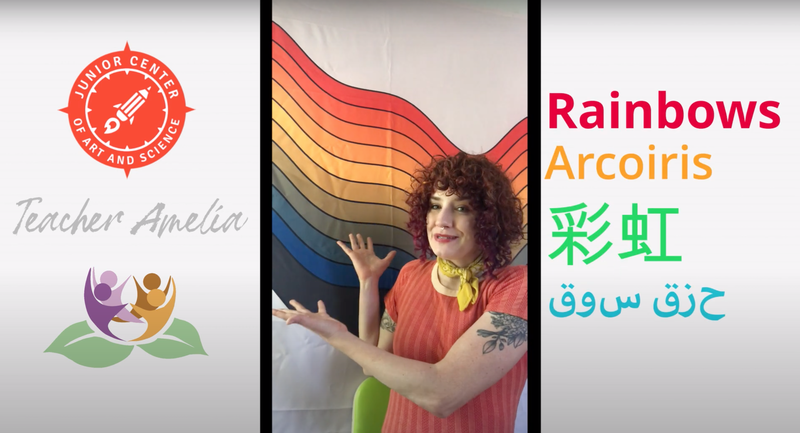 "Teacher Amelia points to a rainbow artwork behind them. Amelia's  image is bordered by the Junior Center and Lotus Bloom logos on the left, and the word ""Rainbow"" in English, Spanish, Chinese and Arabic on their right."