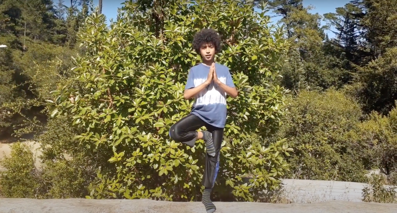 "Sol does a yogic ""tree pose"" in front of a green jasmine bush on a sunny day."