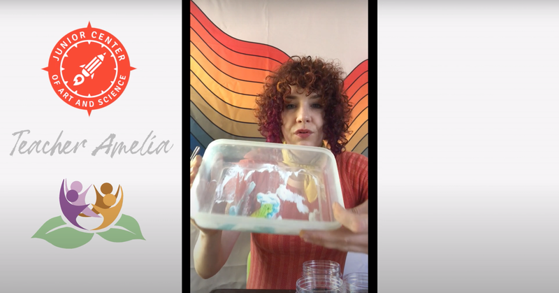 Teacher Amelia shows a container fizzing with baking soda and blue food coloring, and a rainbow wall-art behind them. Amelia's image is bordered with white and the logos of JCAS and Lotus Bloom on the right.